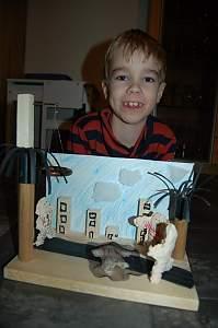 """Stolzer junger Teilnehmerin des Projektes """"Kunstselbstbaupaket"""" neben seinem Kunstwerk mit dem Titel """"Der Helfer"""", Foto privat"""
